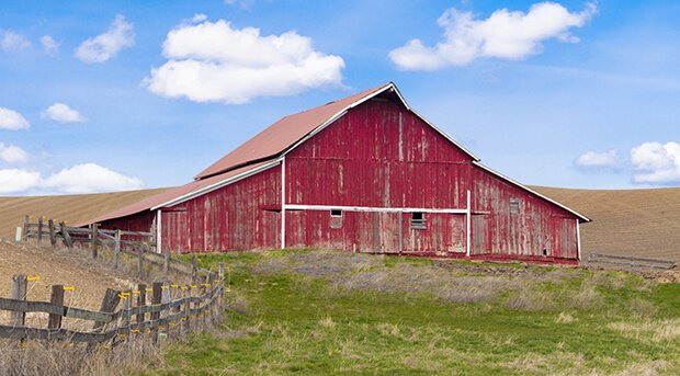 A panorama of red barn under a blue sky near Palouse, Washington.